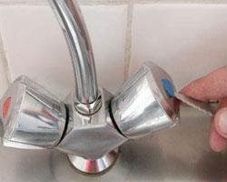 Возле рукоятки смесителя протекает вода